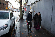 Elderly woman being helped along on a wet day in Leytonstone in East London, United Kingdom. Leytonstone is an area of East London, and part of the London Borough of Waltham Forest.