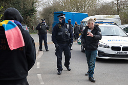 Sipson, UK. 8th March, 2021. A Metropolitan Police officer uses coronavirus legislation to ask a man to vacate the area during an operation to evict residents from the remaining section of a squatted off-grid eco-community garden known as Grow Heathrow. Grow Heathrow was founded in 2010 on a previously derelict site close to Heathrow airport in protest against government plans for a third runway and has since made a significant educational and spiritual contribution to life in the Heathrow villages which are threatened by airport expansion.