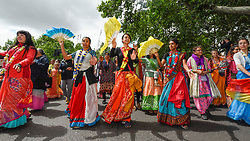 """© Licensed to London News Pictures. 16/06/2019. LONDON, UK.  Women dance at the head of the parade as devotees celebrate the annual Rathayatra festival (""""cart festival""""), in central London.  Hare Krishna followers tow three huge decorated carts from Hyde Park corner to Trafalgar Square, singing and dancing all the way..  Photo credit: Stephen Chung/LNP"""