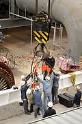 Workers grab crane hook.
