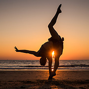 A woman practices her acrobatic routine as the sun goes down on Agonda beach, in south Goa.
