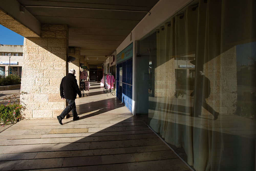 A Jewish man walks past shops at one of the commercial centers of the West Bank Jewish settlement of Efrat in the Gush Etzion settlement bloc, which is situated on the southern outskirts of the Palestinian West Bank city of Bethlehem, on December 30, 2016.