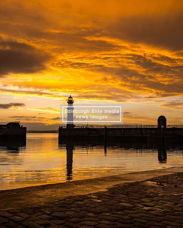 Edinburgh, Scotland, UK, 16th June 2021. Sunset at Newhaven Harbour: People were treated to a colourful sunset this evening with calm water reflecting the colours of the sky.<br /> Sally Anderson   EdinburghElitemedia.co.uk
