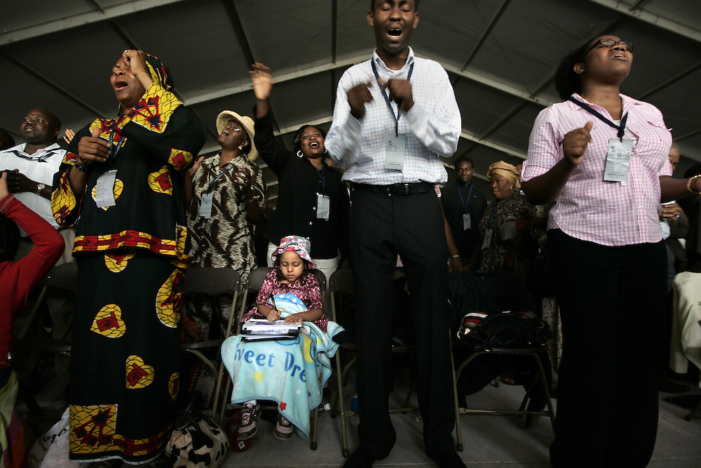 Ezenwanyi Duru, 5, seated, draws while her mother Stella Duru, left, of Houston, and others sing in worship at The Redeemed Christian Church of God's 12th Annual Convention held at Redemption Camp, the land owned by the church in Floyd, Texas, Thursday June 19, 2008.