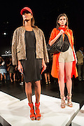 A black dress worn with a snakeskin-patterned jacket, and tangerine hat and matching shoes. A second model wears a bright tangerine raincoat.  By Monika Chiang at Spring 2013 Fashion Week in New York.