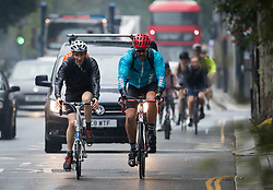 © Licensed to London News Pictures. 13/08/2020. London, UK. Cyclists makes their way through a downpour of rain, on Kensington High Street, West London as the UK experiences thunderstorms and heavy rainfall following days of sunshine and high temperatures. Photo credit: Ben Cawthra/LNP