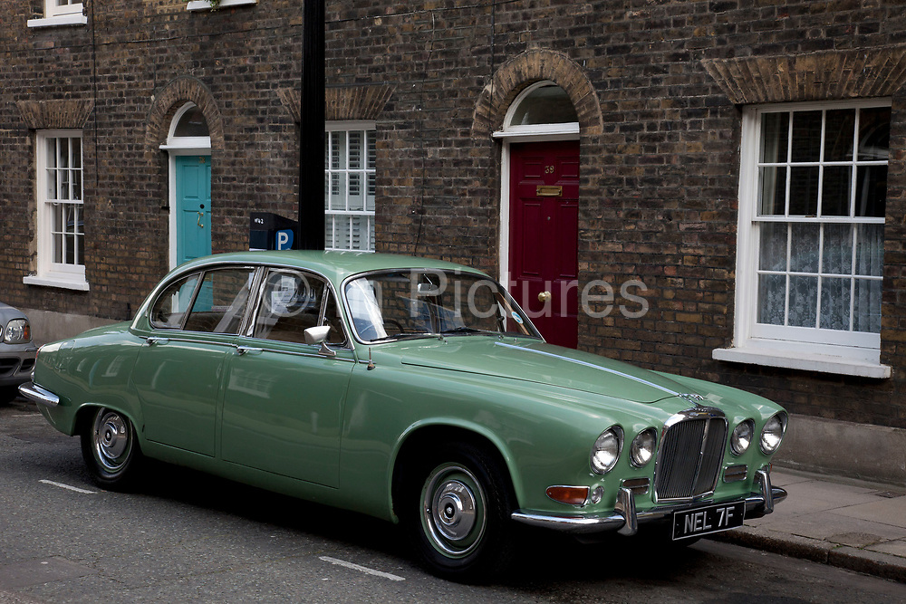"""Old Jaguar car parked on a Georgian terrace street, Roupell Street, Waterloo, London, UK. The Jaguar 420 (pronounced """"four-twenty"""") and its Daimler Sovereign equivalent were introduced at the October 1966."""