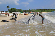 Men with fishing nets on tropical beach at Pasikudah Bay, Eastern Province, Sri Lanka, Asia