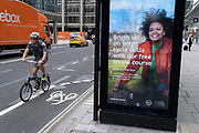 A cyclist on a foldaway bike rides past a digital ad by TFL Transport For London promoting cycling skills at the time of the Coronavirus pandemic - when more Londoners are taking to two wheels as an alternative to the capitals public transport system, on 6th August 2020, in London, England.