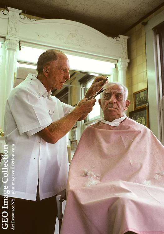 Barber Joe Szarc cutting a customer's hair at the Szarc Barber Shop in the Braddock neighborhood of greater Pittsburgh. Mr. Szarc is over 70 years old and still giving haircuts and shaves, mostly to other older men who are retired from working in the steel mills. Many geriatric people still take pride in personal grooming despite age. The barbershop was started by Mr. Szarc's father.