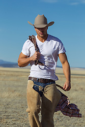 sexy cowboy walking on a ranch