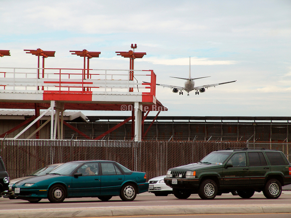 A landing airplane in the vicinity of a highway.