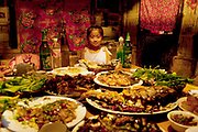 A hungry child with a table covered with food feast at a restaurant in De Hui city, Jilin Province. North Eastern China.
