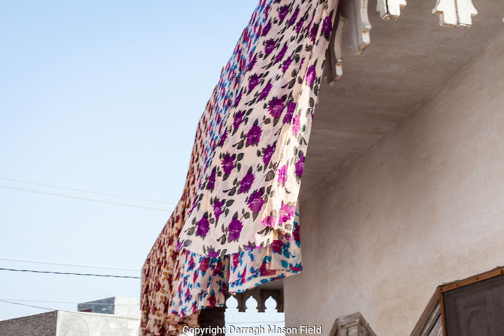 Sari's billowing in the afternoon breeze after soaking in fixing chemicals.