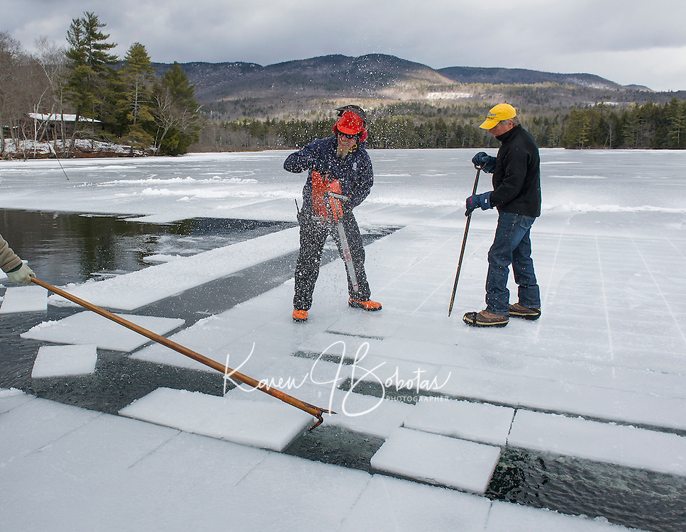 Jon Spence and John Jurczynski break up the cut ice chunks with the crew then channeling them towards the chute for loading during the Rockywold-Deephaven Camp annual ice harvest on Squaw Cove Wednesday.    (Karen Bobotas/for the Laconia Daily Sun)