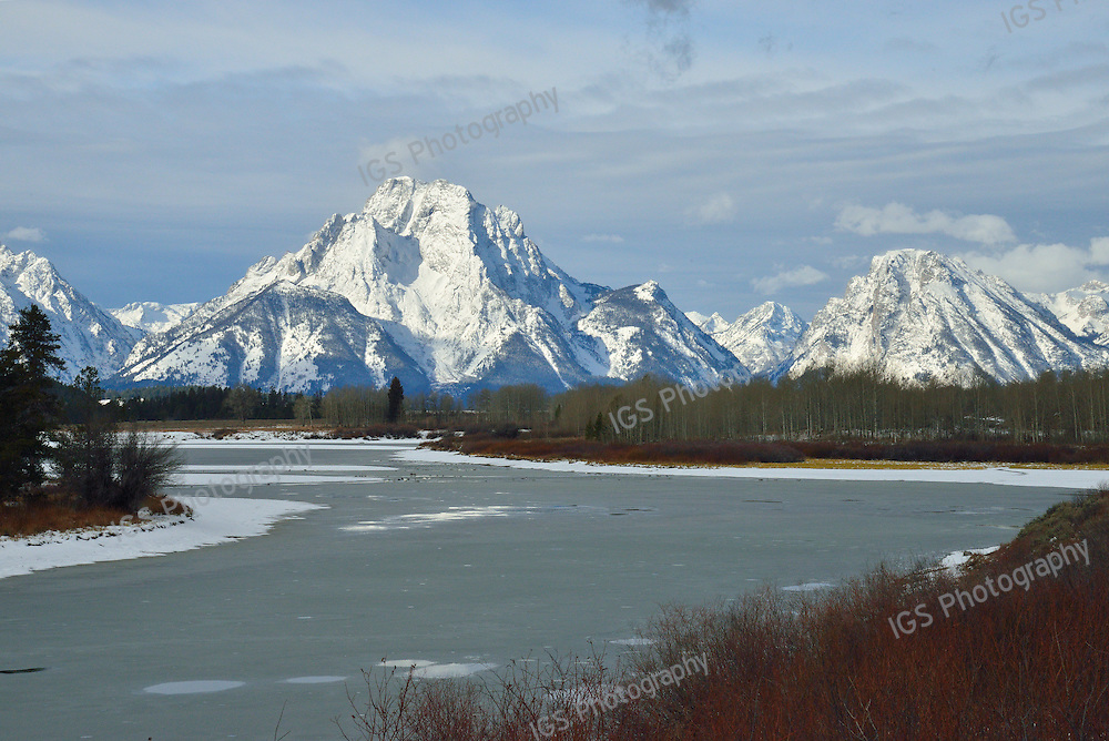Snowcovered Mount Moran and nearby peaks of the Teton range tower above the icy waters at OxBow bend on the Snake River in Grand Teton National Park, Wyoming