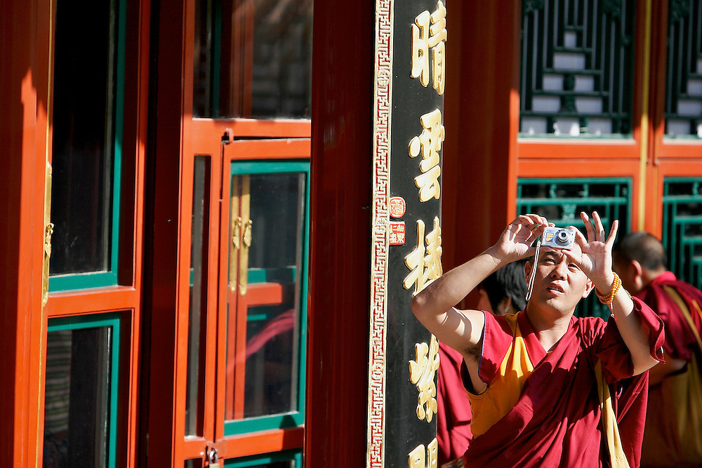 A monk pauses to photograph the Tower of Buddhist Incense a structure inside the Summer Palace.  The Summer Palace in north west Beijing was built in the Jin Dynasty.  The Summer Palace is over 700 acres, 3/4 of which is the Kunming Lake.