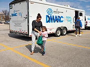 """17 MARCH 2020 - DES MOINES, IOWA: A mother and daughter walk back to their car after getting a bag of food from a Des Moines Area Religious Council (DMARC) food distribution in the parking lot of Carver Elementary School in Des Moines. Des Moines Public Schools are closed for at least 30 days because of the Coronavirus outbreak. Des Moines area religious organizations and food banks are working together to bring free food to children in at risk communities. Volunteers and workers are practicing """"social distancing"""" by leaving the food packages on the pavement and recipients pick up the packages. Tuesday, the Governor of Iowa ordered all restaurants and bars to close or go to take out only. The Iowa Department of Public Health has urged all public buildings, like libraries and schools, to close, and all schools in Iowa are closed for at least 30 days.     PHOTO BY JACK KURTZ"""