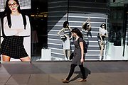 Woman shopper walks past stripe-themed shop window display. Stripes are a style for 2015 and Britain's fashion windows are seemingly full of such designs for the stylish to consider when out buying high street clothes. Three manneqiuins stand in the window of this Oxford Street shop. The woman walking past wears a similar width stripe to the background of the display.