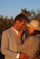 Couple outdoors dressed up and being romantic and playful during a sunset in Joshua Tree, CA