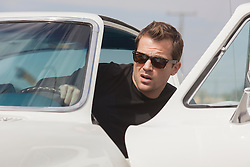 man in Ray Bans and a black tee shirt leaning out of the driver's side of a Corvette with an open door