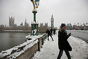 Weather, climate change. London, Britain and Europe, is gripped by a big freeze. Winter conditions which are likened to Siberia swept across Europe, bringing traffic and transport to a halt, closing schools and stopping millions of people going to work. Whilst most buses and tubes were not working, some commuters and tourists got to central London to enjoy the freak snow.///Commuters and tourists walk on across the Thames river to the Westminster and the Houses of Parliament