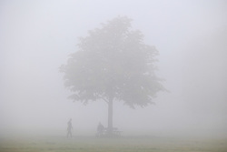 Licensed to London News Pictures. 09/10/2021. London, UK. Walkers enjoy the dense fog on Wimbledon Common south-west London this morning as the Met Office issue yellow weather warnings for fog patches in London and the South East, leading to difficult driving conditions and disruption to travel. Photo credit: Alex Lentati/LNP