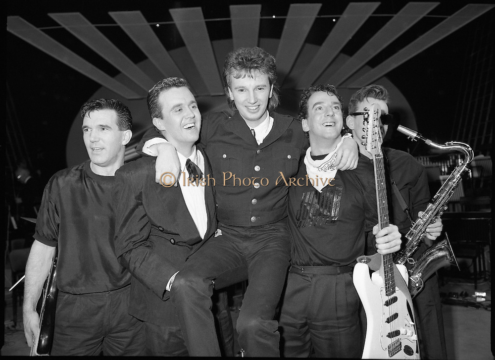 "Eurosong 1988.    (R74)..1988..06.03.1988..03.06.1988..6th March 1988..At the Olympia Theatre, Dublin the Eurosong contest was held last night. The winning song ""Take Him Home"" penned by Peter Eades and performed by the group ""Jump The Gun"". Peter Eades is the keyboard player with the group. As Ireland are the holders, thanks to Johnny Logans win Brussels, ""Jump The Gun"" will represent Ireland at the Simmonscourt in April...Picture shows 'Jump The Gun' celebrating after their win in the Eurosong Contest. (L-R) Brian O'Reilly, Drums; Roy Taylor, Bass; Peter Eades, Composer/Keyboards; Erik Sharpe, Lead Guitar and Kieran Wilde, Sax"