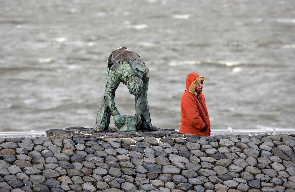 """Nederland Den Oever Zurich 22 november 2008 20081122 Foto: David Rozing ..Serie afsluitdijk. De Afsluitdijk is een belangrijke waterkering en verkeersweg in Nederland. De waterkering sluit het IJsselmeer af van de Waddenzee. Hieraan ontleent de dijk zijn naam. De verkeersweg, onderdeel van Rijksweg a7, verbindt Noord-Holland met Friesland...afsluitdijk ter hoogte van de uitkijktoren. Vouw bekijkt bronzen beeld Steenzetter.Ter gelegenheid van 50 jaar Afsluitdijk werd in 1982 het beeld de """"Steenzetter"""" van Ineke van Dijk geplaatst. Tekst: """" de strijd tegen het water blijft een strijd door en voor de mens """"standbeeld, monument, mensen, bezoekers,  deltaplan...Foto David Rozing"""