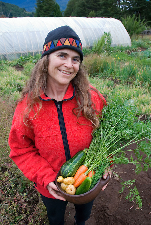 Woman holding vegetables freshly picked from a garden n Chile's Futaleufu River Valley.