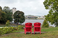 Two Adirondack chairs with a view of the Ottawa River and the Canadian Museum of History (Museum of Civilization) in Québec.<br /> Photographed next to Ottawa Locks 1-8 on the Rideau Canal in Ottawa, Ontario, Canada.