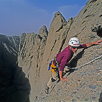 Mountaineer Mark Newcomb climbs treacherous conglomerate rock on Shipton's Arch in the arid Kara Tagh Mountains next to the Taklimakan Desert near Kashagar (Kashi) in Xinjiang Province, China. Later the expedition crossed the range by descending the dangerous and unexplored slot canyon below him.