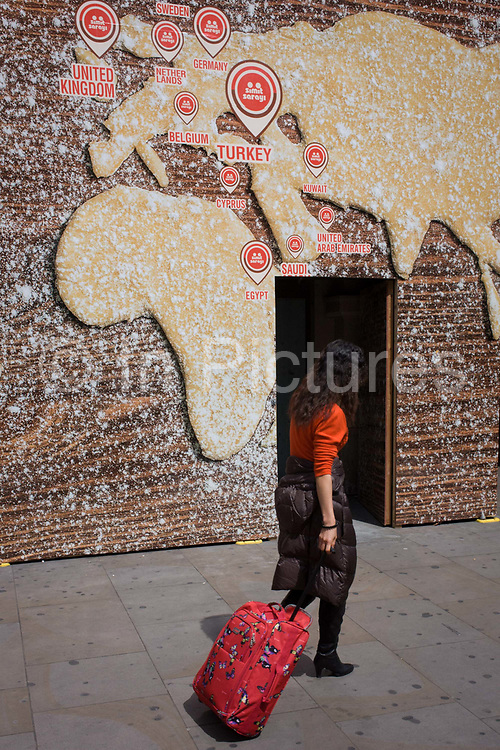 Tourist pulls baggage beneath a world map on a bakery business hoarding. The woman passes beneath the large billboard screening off construction work for a new Turkish bagel business called Simit Sarayi that shows a world map made from dough with a dusted flour covering. Countries from America to Europe and the Middle-east show the locations of the business's presence around the globe. She walks eastwards from Piccadilly Circus. Simit Sarayı started in 2002 with a single store. Today, with hundreds of stores in Turkey and abroad with 10.000 employees to over 650.000 daily visitors.