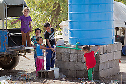 © Licensed to London News Pictures. 25/06/2014. Khanaqin, Iraq. Young Iraqi refugees make use of a water tank provided by the International Red Cross at a refugee camp on the outskirts of Bahari Taza village in Iraq. Located on the outskirts of Khanaqin, a town just 20 minutes from the front-line of the battle with ISIS insurgents, the Bahari Taza refugee camp, and its satellite camps, now house around 600 families from southern Iraq. Built by the local village leader to meet the influx of refugees from nearby Jalawla and Saidia, where intense fighting is still taking place. Turkman, Arab and Kurd, both Sunni and Shia, all live together in tents, barns and unfinished buildings waiting for the conflict to end. Photo credit: Matt Cetti-Roberts/LNP