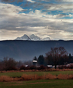 Twin Sisters mountains peer over a farmhouse near the Mount Baker Vineyards. (Ellen M. Banner / The Seattle Times)