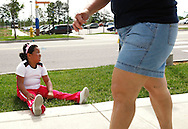 Fernanda Garcia-Villanueva, 8, rests as another participant keeps walking in the annual run/walk for patients and their friends and families at The Children's Hospital in Aurora, Colorado June 5, 2010.  The run/walk is for patients in the various weight management programs at the hospital. REUTERS/Rick Wilking (UNITED STATES)
