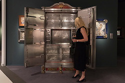 """© Licensed to London News Pictures. 29/06/2017. London, UK.  A staff member presents """"An Exclusive Jubilee Fire Resistant Safe"""", 1869, by F. Wertheim & Co.  Members of the public visit Masterpiece London, a leading art fair held in the grounds of the Royal Hospital Chelsea.  The fair brings together 150 international exhibitors presenting works from antiquity to the present day and runs 29 June to 5 July 2017.  Photo credit : Stephen Chung/LNP"""