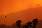 7 May 2009 - Santa Barbara, CA -  Water dropping helacopters fly over the  Jesusita fire as it burns homes in the foothills of Santa Barbara, California. Photo Credit: Rod Rolle/Sipa Press,  21 August 2009-Santa Barbara, CA: