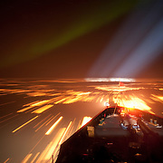 The bow of the Polar Sea icebreaker at night with northern lights just above the horizon. A spotlight from the ship helps guide it through the ice. Arctic Ocean