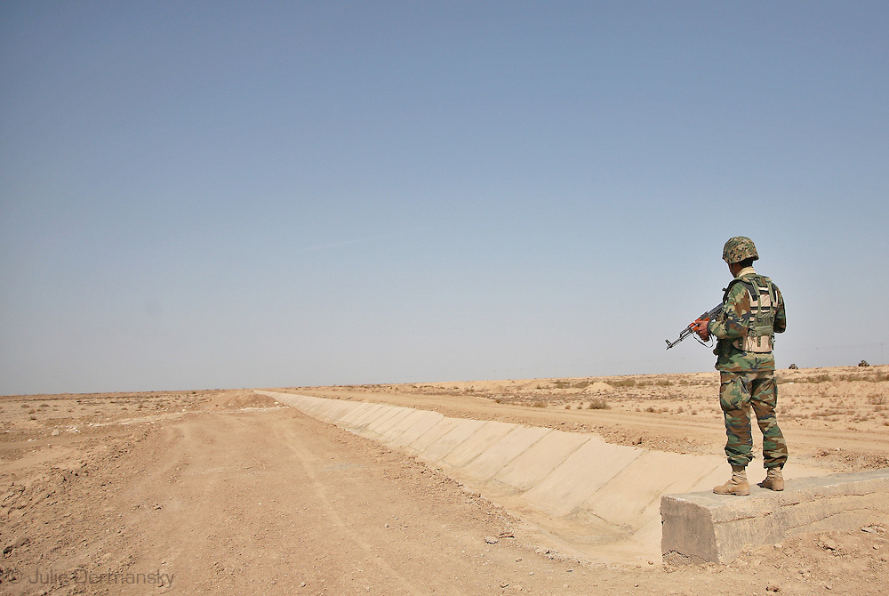Barren landscape in what was once the marshland's of iraq in the south near the iranian border. Iraqi soldier, one of a large security team, guard the road as a generals' convoy drives by.