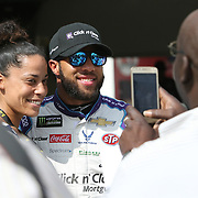 Darrell Wallace Jr., driver of the (43) Click n' Close Chevrolet,  is seen posing with fans in the garage area during practice for the 60th Annual NASCAR Daytona 500 auto race at Daytona International Speedway on Friday, February 16, 2018 in Daytona Beach, Florida.  (Alex Menendez via AP)