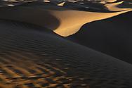 Abstract desert sand dunes with deep shadows before sunset. Sahara desert, Mhamid, Morocco.