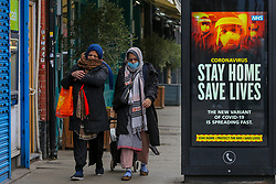 © Licensed to London News Pictures. 10/01/2021. London, UK. Asian women wearing protective face coverings walk past the Government's 'Stay Home, Save Lives' Covid-19 publicity campaign poster in north London, as the number of cases of the mutated variant of the SARS-Cov-2 virus continues to spread around the country. The message in the advertising campaign poster says 'The new variant of Covid-19 is spreading fast'. <br /> Almost 60,000 new cases of coronavirus were reported in the UK on Saturday 9 January 2021 and the number of deaths after a positive test passed 80,000, since the pandemic began. Photo credit: Dinendra Haria/LNP