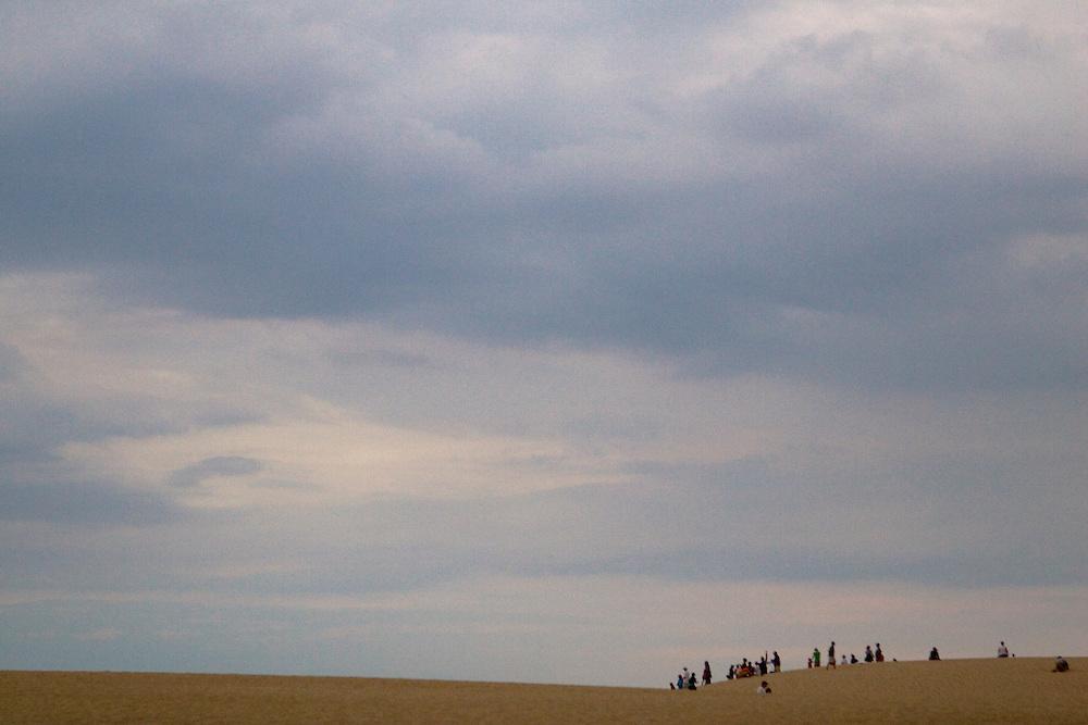 A group gathers on dunes at Jockey's Ridge National State Park, North Carolina.