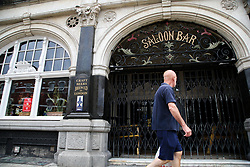 © Licensed to London News Pictures. 20/06/2020. London, UK. A man walks past 'The Salisbury Hotel' pub on Green Lanes, Haringey, north London. Pubs, restaurants and cafes will  reopen on 4 July. 'The Salisbury Hotel' pub has been closed since 23 March following the coronavirus lockdown. The government has lowered COVID-19 alert level from four to three raising expectations that 2 meter distancing restrictions could be cut.  Photo credit: Dinendra Haria/LNP