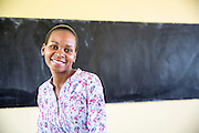 Local teacher Rebecca Ngovano sitting in front of a blackboard in one of the classrooms of Angaza school, Lindi, Tanzania