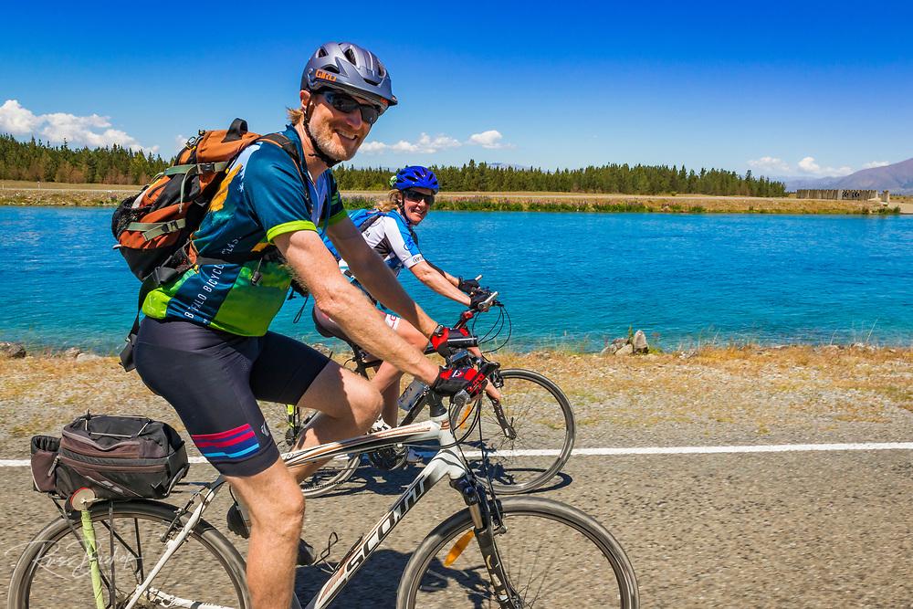 Cyclists riding along the Pukaki Canal, Ben Ohau, Canterbury, South Island, New Zealand