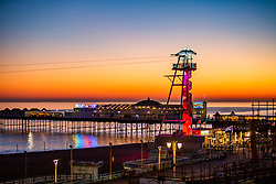 © Licensed to London News Pictures. 26/02/2019. Brighton, UK. The Brighton Palace Pier and Brighton Zipwire attraction stand infant of a colourful sky as the sun sets over Brighton and Hove. Photo credit: Hugo Michiels/LNP
