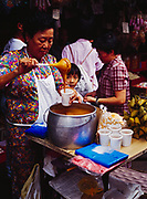 Woman serving food at street market in Chinatown section of Kuala Lumpur, Malaysia.