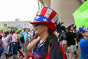 """Kathy Carver who emigrated from France dons a brightly colored hat during the Familes Belong Together rally in downtown Dallas. """"I came to America for everything it is. This is not America. We need to change that."""" she said."""